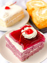 Sweet dessert cake with mousse whipping cream and cherry on top shallow depth of field with focus on the cherry Stock Photos