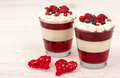Sweet dessert in glass with cream, jell, raspberries and blueberries on wooden background. Royalty Free Stock Photo