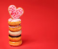 Sweet donuts with heart shaped donut on the top over red Royalty Free Stock Photo