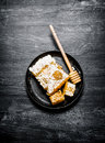 Sweet flavored honey in the comb with a spoon pan on black rustic background Stock Image