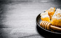 Sweet flavored honey in the comb with a spoon pan on black rustic background Stock Photography