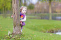 Sweet funny toddler girl hiding behind tree in park a a beautiful autumn Stock Photo