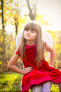 Sweet girl in the autumn forest on chair Royalty Free Stock Image