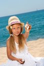 Sweet girl on beach showing shell. Royalty Free Stock Image