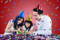 Sweet girl cuts birthday cake happy celebrate her and cutting with her parents Royalty Free Stock Photo