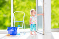 Sweet girl washing a window cute laughing curly toddler big with squeegee in beautiful white living room with door into the garden Royalty Free Stock Photos