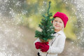 Sweet Girl Wearing Mittens Holding Small Christmas Tree with Snow Effe Royalty Free Stock Photo