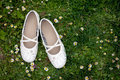 Sweet girlie white shoes on a lawn in garden Royalty Free Stock Photos