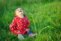 Sweet happy little girl sitting in grass outdoor. Cute baby with curly hair laughting. Young girl posing in park. Smiling kid.