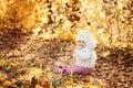 Sweet kid sitting on the autumn leaves