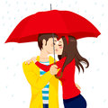 Sweet kiss under umbrella couple in love hugging and kissing big red on a rainy day Royalty Free Stock Photo