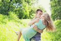 Sweet kiss young couple outdoors, man and woman in love, he holds her on hands at grass Royalty Free Stock Photo