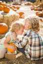 Sweet little boy kisses his baby sister at pumpkin patch in a rustic ranch setting the Stock Photography