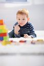 Sweet little boy lost in playing laying on floor with building cubes thinking Royalty Free Stock Image