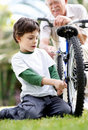 Sweet little child fixing his bicycle Royalty Free Stock Image