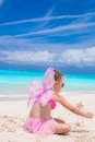 Sweet little girl with butterfly wings on white beach Royalty Free Stock Photo