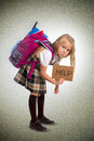 Sweet little girl carrying very heavy backpack or schoolbag full young blonde schoolgirl holding help sign school bag causing Stock Photography