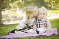 Sweet little girl kisses her baby brother at the park on his cheek outdoors Stock Photography