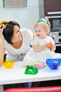 Sweet little girl and mother having fun in a kitchen Royalty Free Stock Photography
