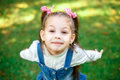 Sweet little girl outdoors with curly hair in two long tails, closeup portret.