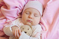 Sweet Little Newborn Baby Sleeping On The Blanket With His teddy bear Toy