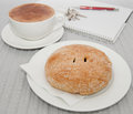 Sweet pastry and cappucino on white servingware in front of notebook keys and pen Royalty Free Stock Images