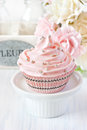 Sweet pink cupcake on a cake stand Royalty Free Stock Image