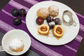 Sweet plum dumplings and fresh plums in white plate on table Stock Images