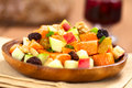 Sweet potato and apple salad fresh made of cooked potatoes fresh apples nuts raisins shallots on wooden plate with mulled wine in Royalty Free Stock Photos