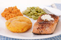 Sweet potato biscuit on white plate with baked salmon steak lima beans and candied yams strong light on white background Royalty Free Stock Image