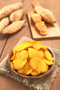 Sweet potato chips crispy peruvian on wooden plate with potatoes in the back selective focus focus one third into the Stock Images