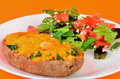 Sweet potato stuffed with shrimp twice baked and sautted spinach on plate garden salad against orange color Royalty Free Stock Images