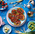 Sweet potato toast with beet hummus, grilled chickpeas, fresh parsley, nigella seeds and sunflower seeds on a plate on a blue ta Royalty Free Stock Photo