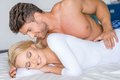 Sweet sexy caucasian couple lying on white bed close up smiling Royalty Free Stock Photos