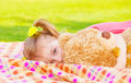 Sweet small girl laying down on the meadow with big soft toy happy childhood day care spring time fun Royalty Free Stock Photo