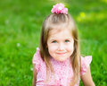 Sweet smiling little girl with long blond hair sitting on grass in summer park closeup outdoor portrait Stock Photography