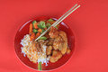 Sweet and sour chicken on red plate against red background Royalty Free Stock Image