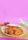Sweet and sour chicken vertical dinner in chinese restaurant setting on bamboo cane place mat design on plate colorful background Stock Image
