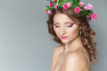 Sweet sweet beautiful sexy young girl with a wreath of flowers on his head with bare shoulders with beauty makeup soft pink lips