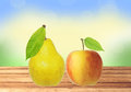 Sweet tasty apple and pear on wooden table over nature backgroun the background Royalty Free Stock Photography