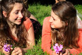 Sweet teen bff girls two pretty with long brown hair lounging in the grass hanging out talking together shallow depth of field Royalty Free Stock Photography