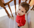 Sweet toddler boy walking down carpeted stairs looking up with a Royalty Free Stock Photo