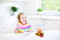 Sweet toddler girl with curly hair having breakfast Royalty Free Stock Photo
