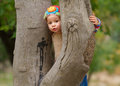 Sweet toddler girl hiding behind the tree Royalty Free Stock Image