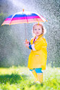 Sweet toddler with umbrella playing in the rain Royalty Free Stock Photo