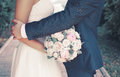Sweet wedding couple with gentle bouquet of peonies flowers, sensual groom hugging lovely bride Royalty Free Stock Photo