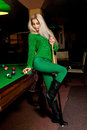 Sweet young blonde girl posing at pool table with the cue in han Royalty Free Stock Photo