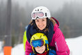 Sweet young boy and his mother, learning to ski on a mild ski sl Royalty Free Stock Photo