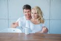 Sweet young couple in white having morning coffee Royaltyfri Fotografi