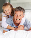 Sweet young girl playing with her father at home Stock Images